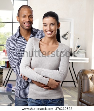 Happy young interracial loving couple hugging and smiling at home, looking at camera. - stock photo