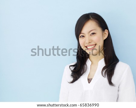 Happy young japanese girl isolated on blue background - stock photo
