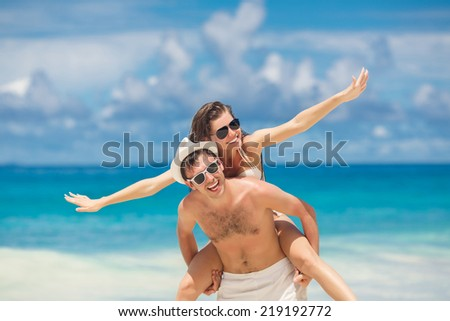 Happy young joyful couple having beach fun piggybacking laughing together during summer holidays vacation on tropical beach. Beautiful energetic fresh interracial multi-ethnic couple, man and woman. - stock photo