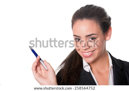 Happy young lady at desk pointing with pen, isolated on white