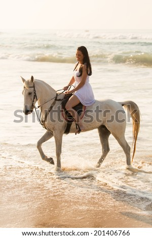 happy young lady enjoying horse ride on beach - stock photo