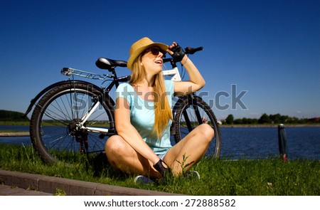 Happy young lady relaxing on a green meadow after cycling - stock photo