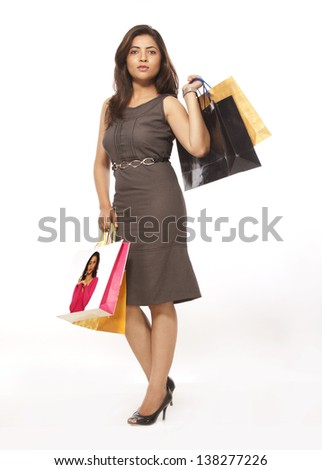 Happy young lady with colorful shopping bags over white background