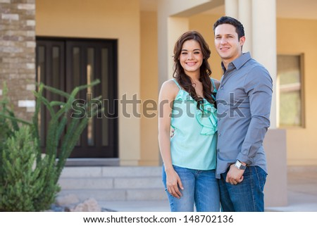 Happy young Latin couple in front of their new house - stock photo