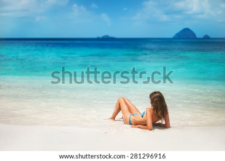 Happy young long haired woman  lying on thetropical  beach and take sunbath - stock photo