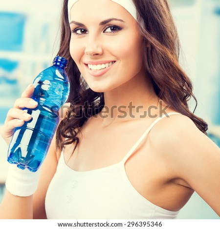 Happy young lovely woman with bottle of water, at fitness club or gym - stock photo