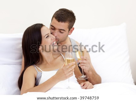 Happy young lovers drinking champagne in bed