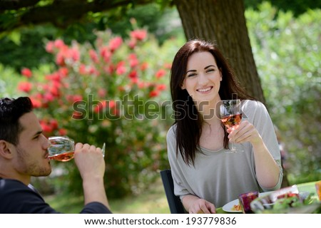 happy young loving couple cheering at lunch barbecue party outdoor in the garden - stock photo