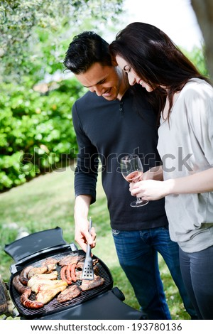 happy young loving couple cooking  together at barbecue party with a glass of wine in summertime - stock photo