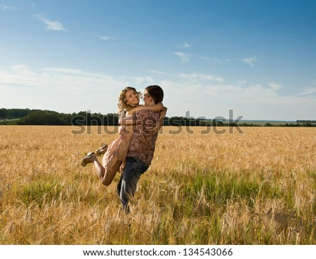 Happy young loving couple on field - stock photo