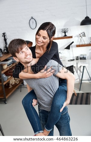 Happy young loving couple piggyback at home.