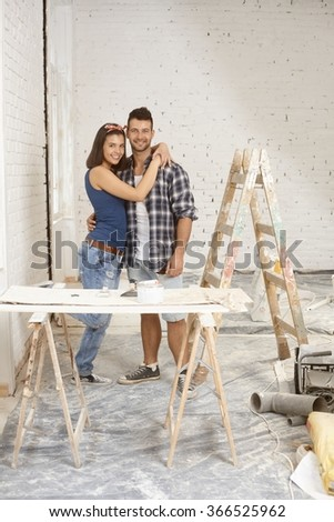 Happy young loving couple renovating home. - stock photo