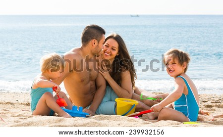 Happy young loving parents with two kids resting at beach - stock photo