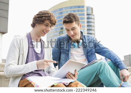Happy young male college students using digital tablet against building - stock photo