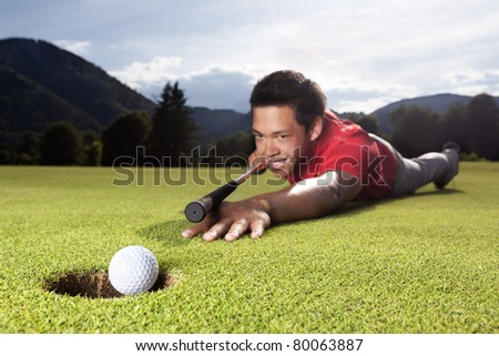 Happy young male golf player lying on green and using golf club as billiard cue (queue) to hole ball into cup. - stock photo