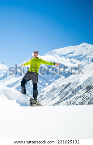 Happy young male hiker with arms outstretched in white winter mountains Himalayas.  Success climbing on snow, beautiful landscape with Annapurna peak in background