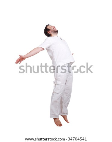 Happy young male in white clothes is jumping with hands up - stock photo