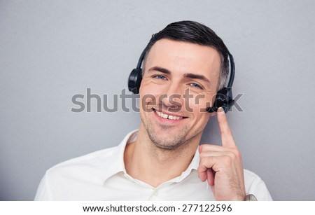 Happy young male operator in headphones looking at camera. Standing over gray background - stock photo