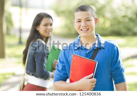 Happy young male student looking at camera - stock photo