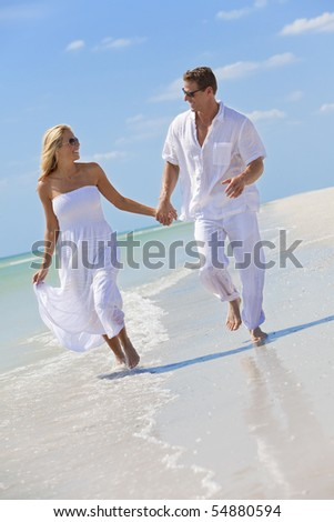 Happy young man and woman couple running, laughing and holding hands on a deserted tropical beach with bright clear blue sky