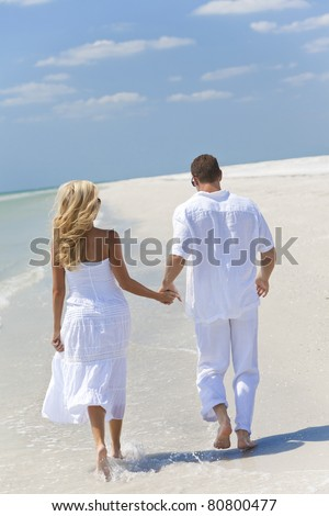 Happy young man and woman couple running or walking and holding hands on a deserted tropical beach with bright clear blue sky - stock photo