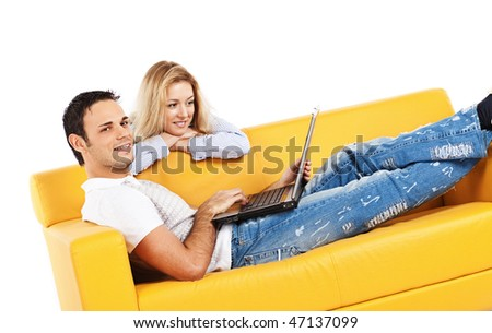 Happy young man and woman sitting together on yellow sofa; isolated on white