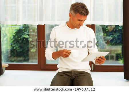 Happy young man at home drinking coffee and reading news on his electronic tablet - stock photo