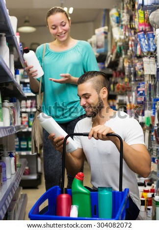 Happy young man buying shampoo in shopping mall - stock photo