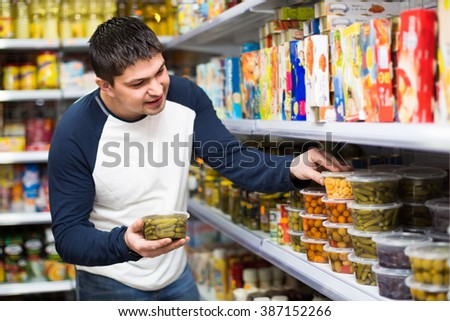 Happy young man buying tinned food at grocery store - stock photo