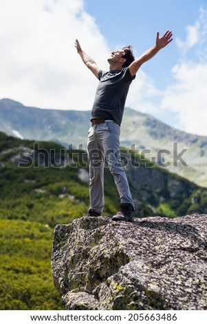 Happy young man celebrating freedom on the mountains - stock photo