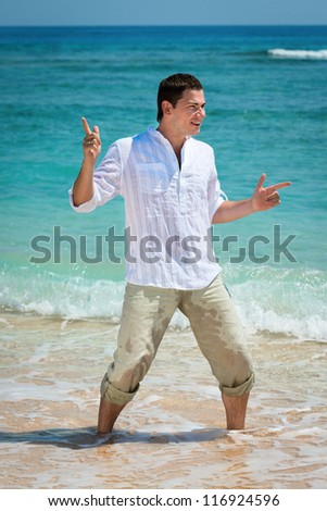 Happy young man dancing at the tropical beach in blue sea water - stock photo