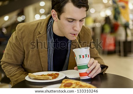 Happy Young Man Eating Pizza At The Food Court In A Mall - stock photo