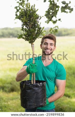 Happy young man gardening for the community on a sunny day - stock photo