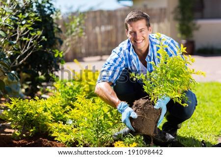 happy young man gardening in backyard - stock photo