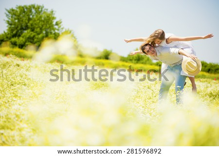 Happy young man giving a piggy back to her girlfriend in Daisy, chamomile field.Copy space - stock photo