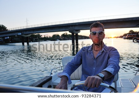 happy young man have fun at boat at sunset on summer season - stock photo