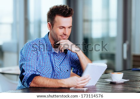 Happy young man having a coffee and thinking - stock photo