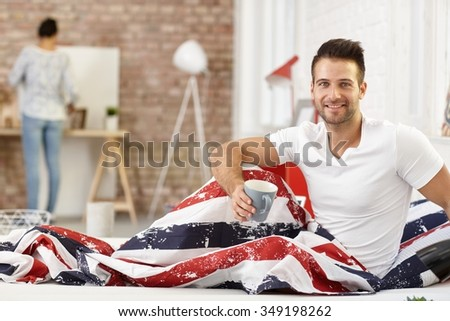 Happy young man having morning coffee in bed, smiling, looking at camera. - stock photo