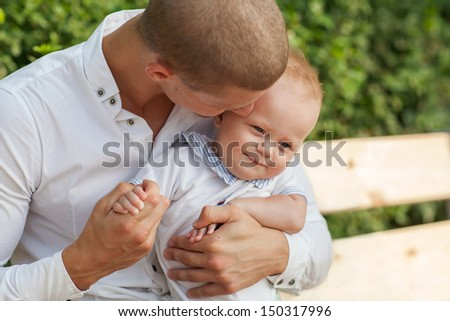 Happy young man holding a smiling 7-9 months old baby - stock photo
