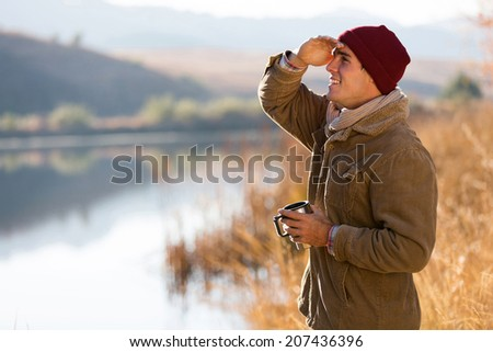 happy young man holding coffee mug and looking into distance in winter morning - stock photo