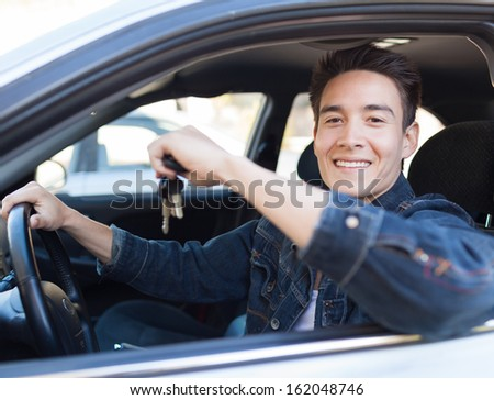 Happy young man holding keys to new car