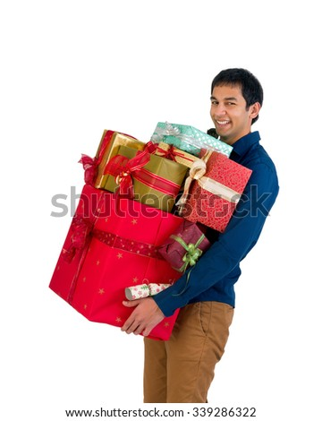 Happy young man holding too many Christmas presents - stock photo