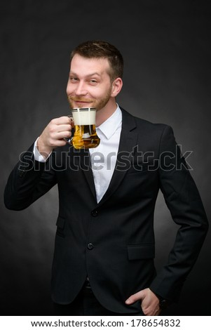 happy young man in a black suit holding a beer mug over a dark background - stock photo