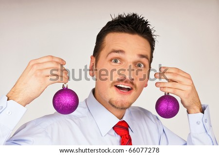 Happy young man in shirt and red tie shows violet Christmas Ornament - stock photo