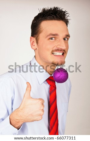 Happy young man in shirt and tie has violet Christmas Ornament between teeth and shows with thumb yes. - stock photo