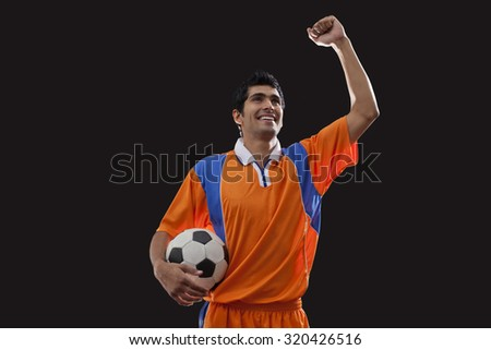 Happy young man in sports clothing celebrates victory while holding ball over black background - stock photo