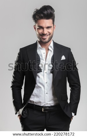 Happy young man in tuxedo holding his hands in pocket, smiling for the camera. On grey background. - stock photo