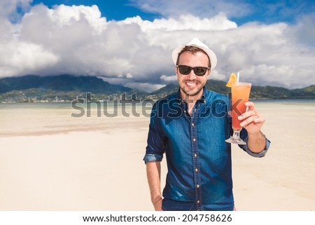 happy young man invites you to a cold drink on the beach and saying cheers! - stock photo