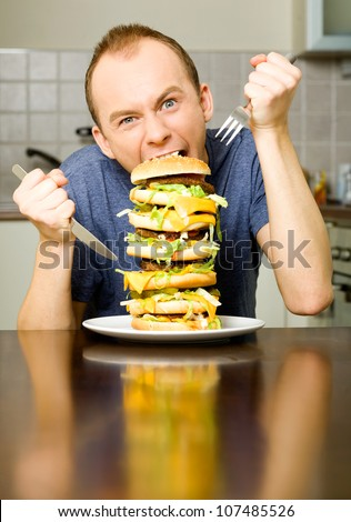 Happy young man is going to eat big layered cheeseburger - stock photo