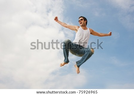 Happy young man jumping against blue sky - stock photo